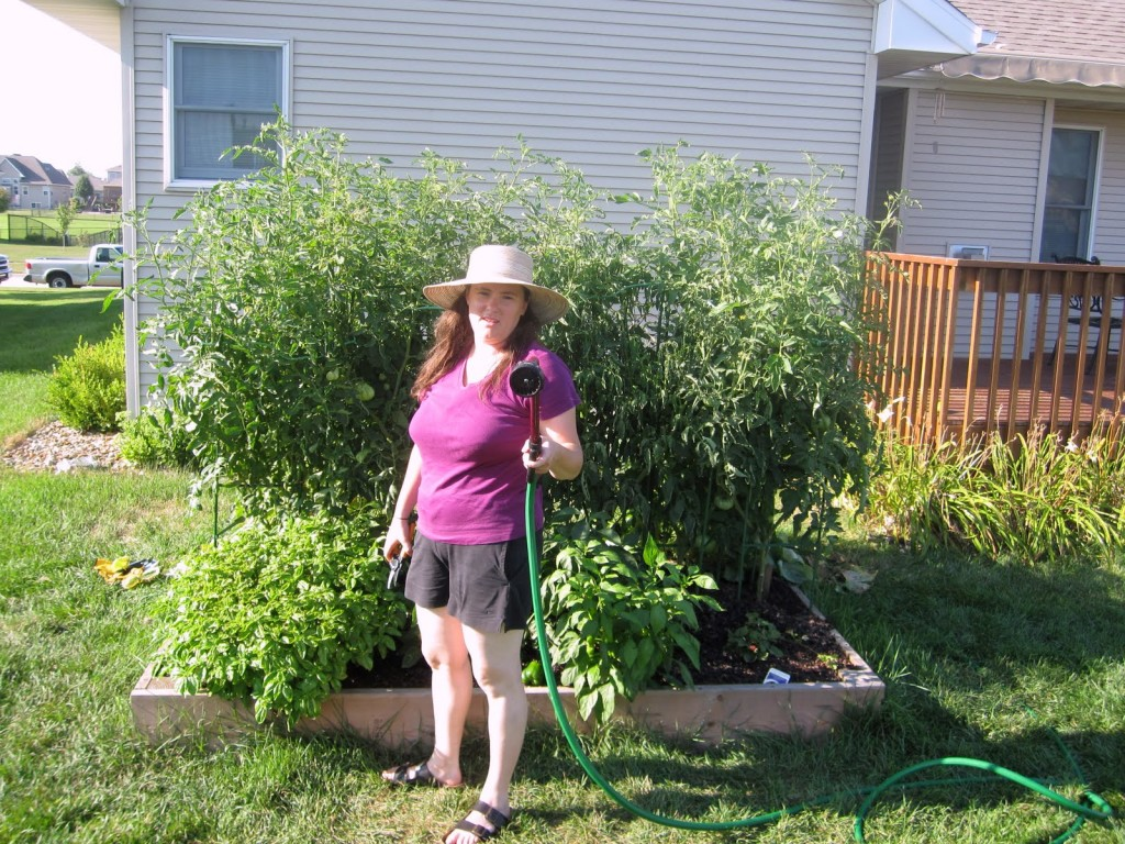 Photograph of Rebeka brandishing a water hose in front of a garden with tall tomato plants.