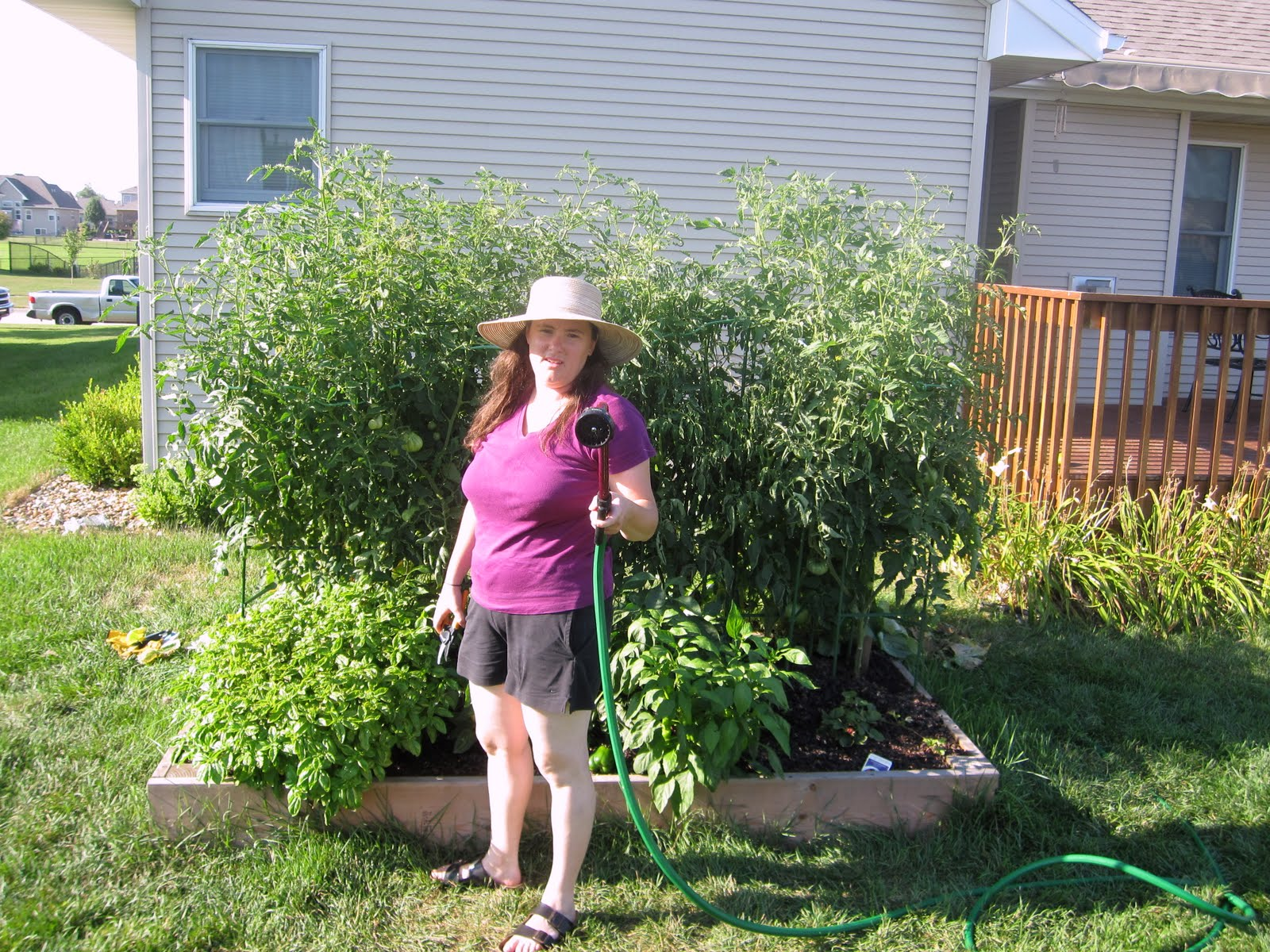 Photograph Of Rebeka Brandishing A Water Hose In Front Of A Garden With Tall  Tomato Plants