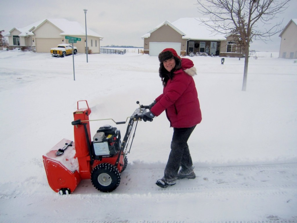 Photograph of a woman using a snowblower.