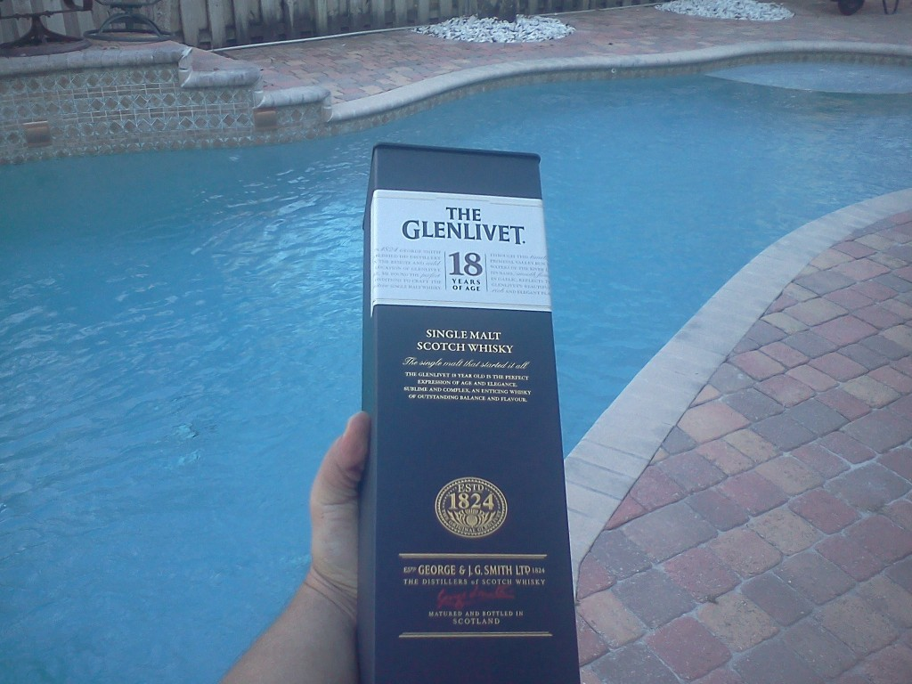 Photograph of a bottle of Glenlivet 18 and a swimming pool in the background.